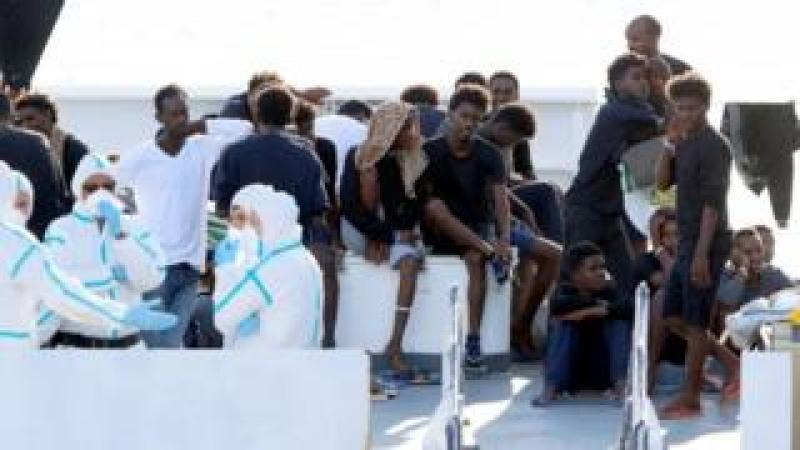 Migrants wait to disembark Italy's coastguard vessel at the port of Catania. Photo: August 2018