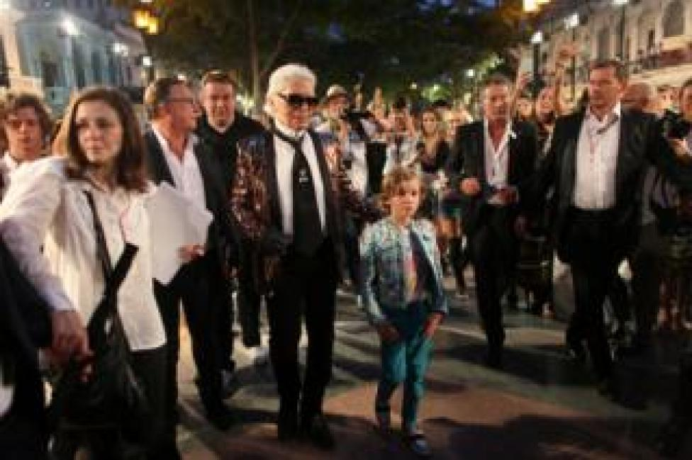 Karl Lagerfeld head designer and creative director of fashion house Chanel, walks with a model after a fashion show of his latest inter-seasonal Cruise collection, at the Paseo del Prado street in Havana, Cuba.