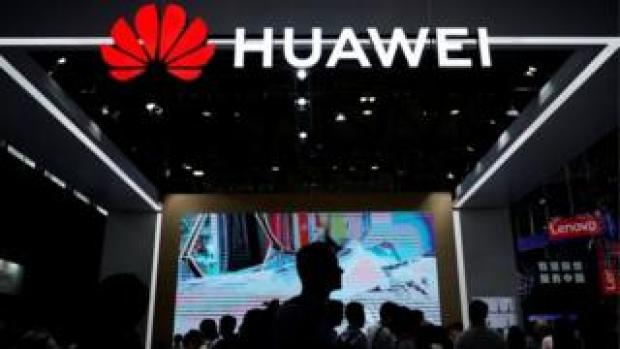People walk past Huawei stall