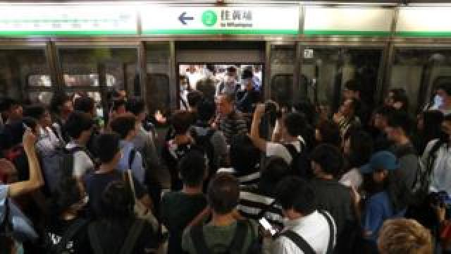 Train passengers wait as Anti-extradition bill protesters disrupt train services