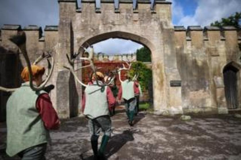 Men holding antlers walk through an arch.