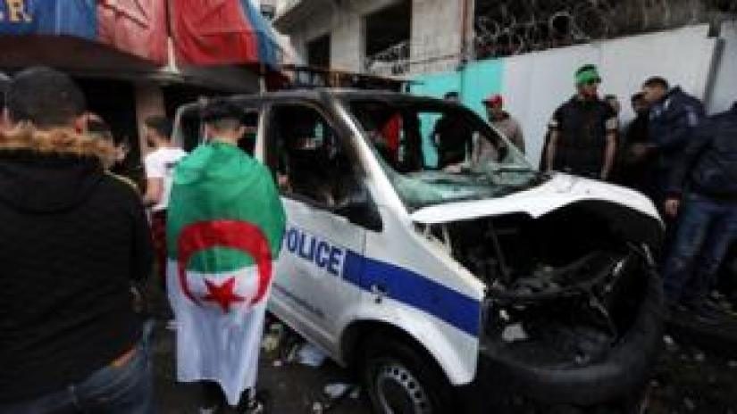 Protesters stand near a burnt-out police van in Algiers, April 2019