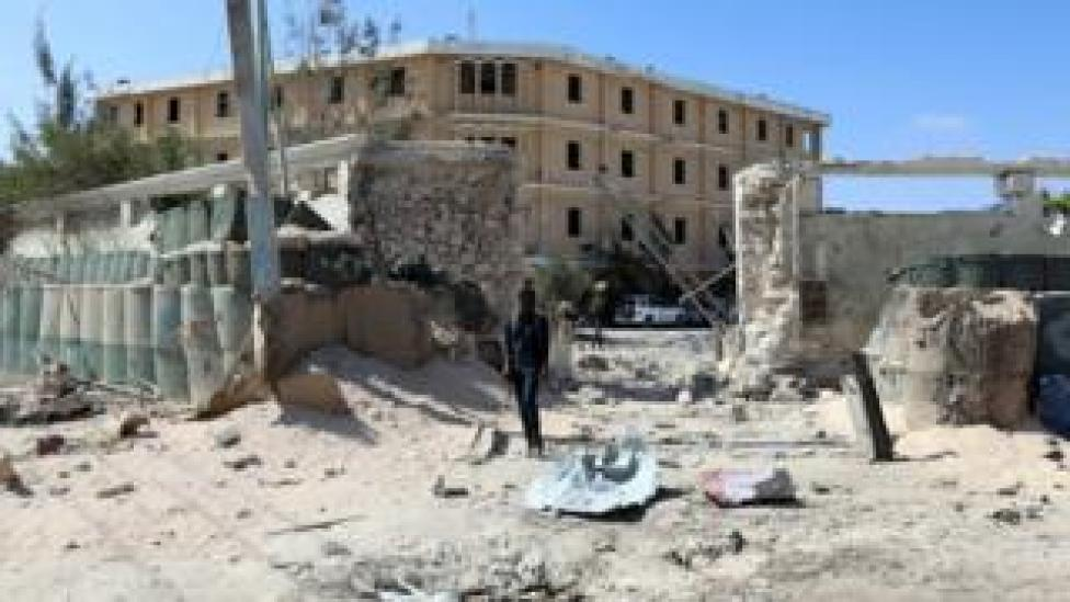 Policemen security forces secure the scene where al-Shabab militia stormed a government building in Mogadishu