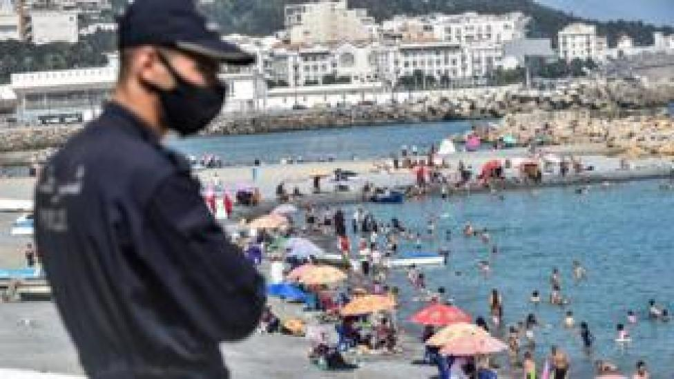 A policeman, mask-clad due to COVID-19 coronavirus pandemic, watches as people cool off in the water at el-Kettani beach in the Bab el-Oued suburb of Algeria's capital Algiers on August 15, 2020.
