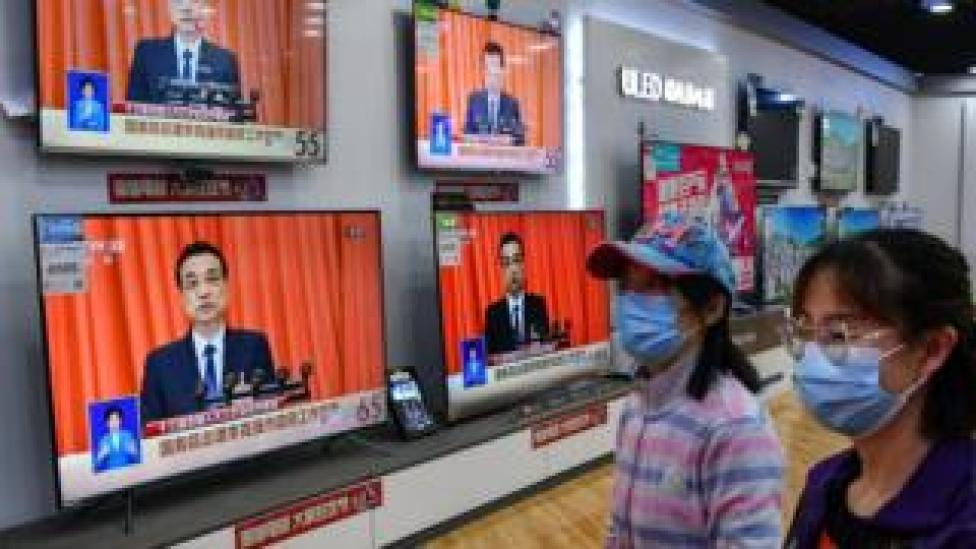 Shoppers walking past a broadcast of Chinese Premier Li Keqiang delivering his speech at the opening of the NPC