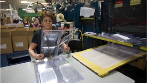 A woman works at a plastic food packaging factory in the US