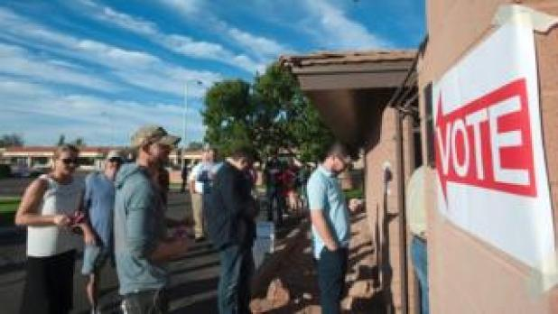Voters wait in line in front of a polling station to cast their ballots in the US presidential election in Scottsdale, Arizona on 8 November 2016