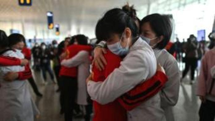 Medical personnel from Jilin Province (red) embrace nurses in Wuhan after the isolation of Covid-19 is lifted, April 8, 2020