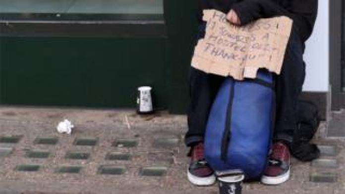 Homeless person with sign saying 'Homeless, £1 towards a hostel Thank you'
