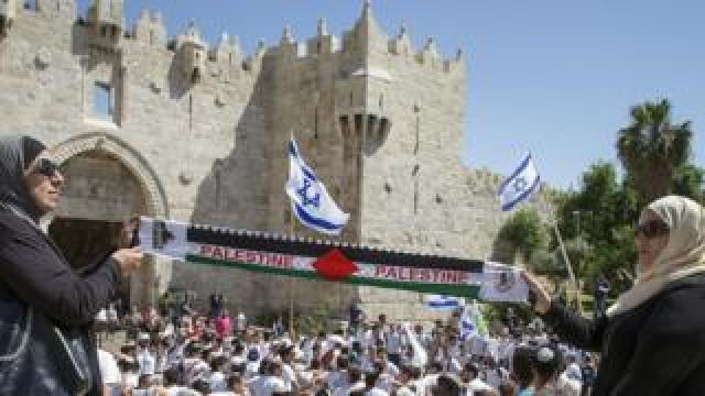 """Palestinian women hold """"Palestine"""" scarf as Israeli youth dance outside walls of Old City in Jerusalem (file photo)"""