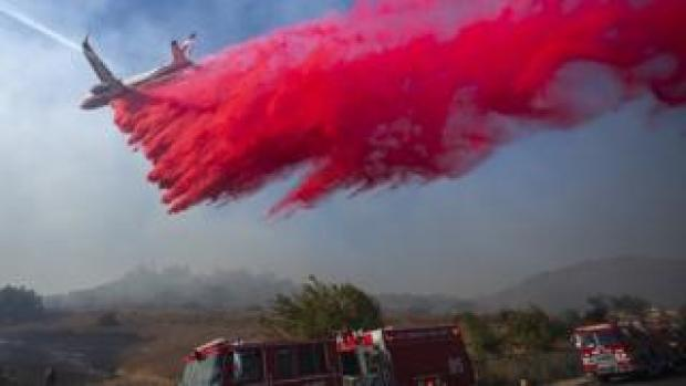 A firefighting jet drop retardant over a threatened neighbourhood at the Easy Fire on October 30, 2019 near Simi Valley, California