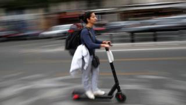 A woman rides a dock-free electric scooter in a Paris street in September 2019