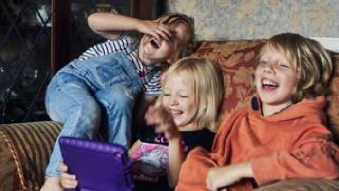 Children laughing on a sofa