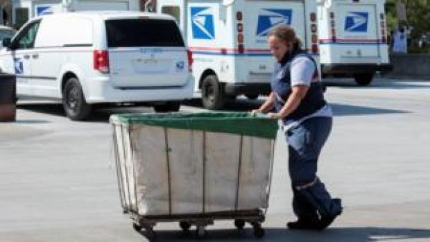 US Postal Service worker pushes a mail bin outside a post office in Royal Oak, Michigan (22 August 2020)