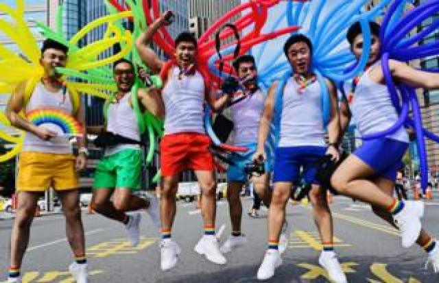 Participants jump in a pose while taking part in the annual Pride parade in Taipei