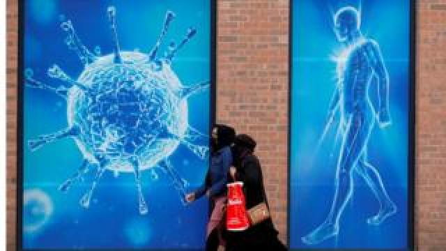 Two women walk past an illustration of a virus in Oldham