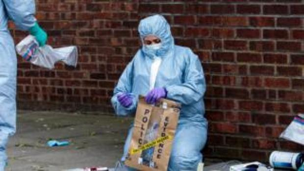 Forensic worker seals up evidence in bag
