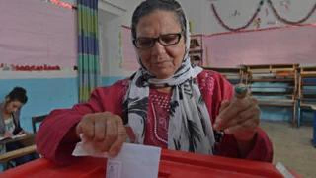 A Tunisian voter casts her ballot at a polling station in the capital Tunis on October 13, 2019 during the second round of the presidential election