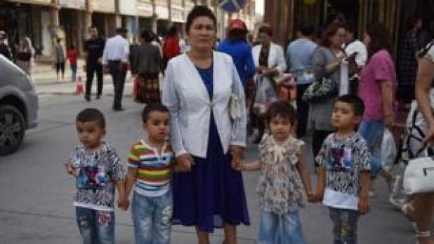 امرأة من الإيغور تنتظر مع أولادها في شارع بكشغار، شمال غرب منطقة شينغيانغ في الصين