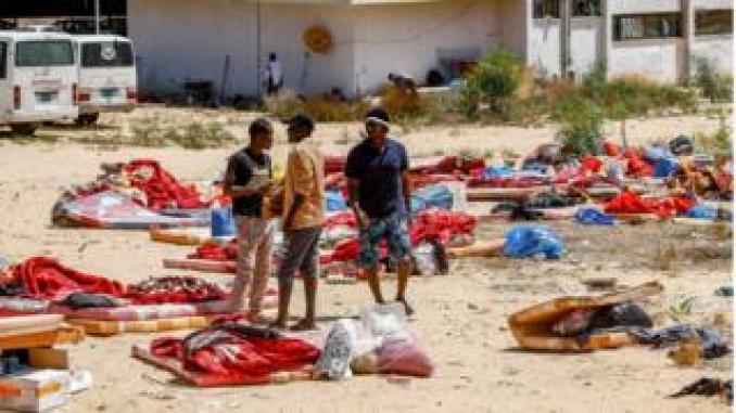 """Migrants stand and walk outside at a detention centre used by the Libyan Government of National Accord (GNA) in the capital Tripoli's southern suburb of Tajoura on July 3, 2019, following an air strike on a nearby building that left dozens killed the previous night. - Over 40 migrants were killed in an air strike early late on July 2 on their detention centre in a Tripoli suburb blamed on Libyan strongman Khalifa Haftar, who has been trying for three months to seize the capital. The UN said the air strike """"may amount to a war crime"""". More than 130 people were also wounded in the in the raid on Tajoura, the statement added. ("""