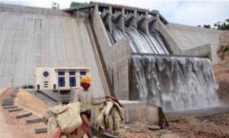 A worker in front of a large hydropower dam in Kampot province