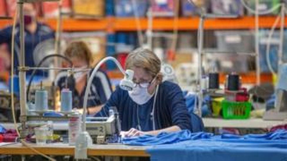 A masked worker making NHS scrubs