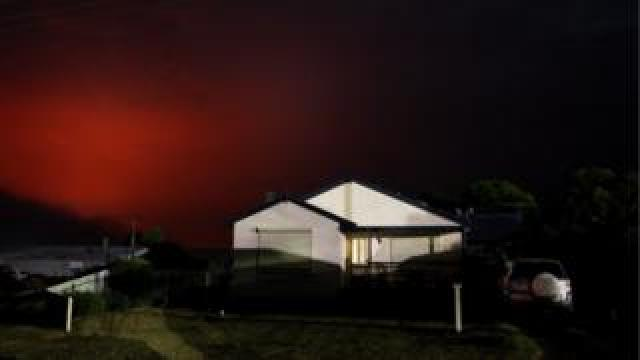 Nearby fire turns the sky dark red over a house in Kingscote on 10 January