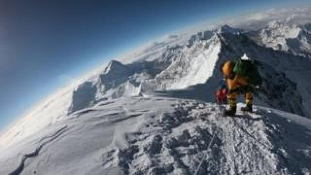 Mountaineers make their way to the summit of Mount Everest,