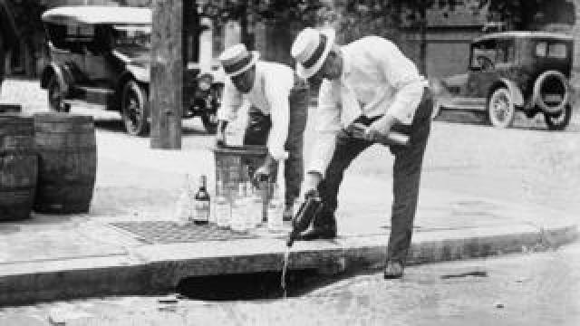 Agents pouring confiscated alcohol down the sewer, circa 1921