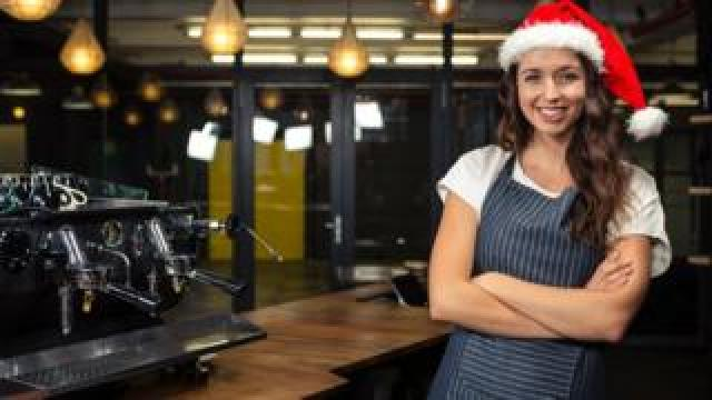 A woman working in a coffee shop wearing a Santa hat
