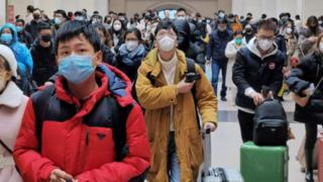People wear face masks as they wait at Hankou Railway Station in Wuhan, China.