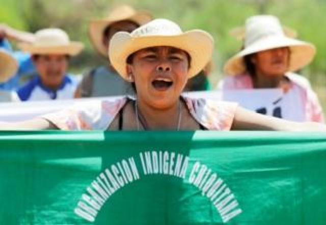 A woman shouts and holds up a banner reading Chiquitanía Indigenous Organisation during the protest march