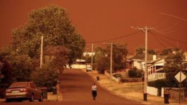 A woman walks down a street in Bruthen, Victoria, beneath an orange sky