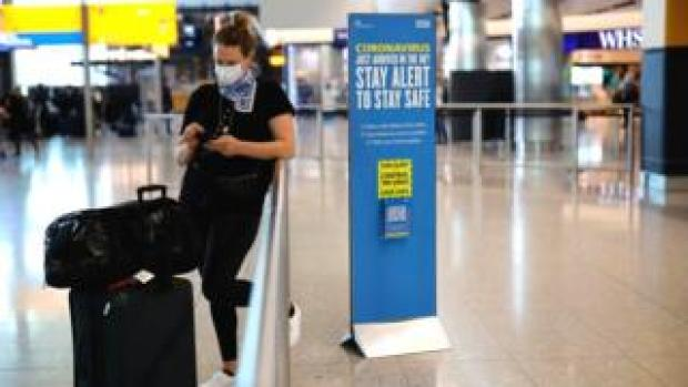 A woman wearing a mask in the departures hall at Heathrow Airport, standing next to a sign