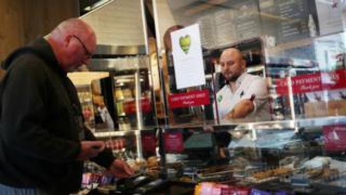 An employee is seen behind a protective screen while serving a customer in a Pret a Manger store which reopened for delivery and take out at Wimbledon on May 1.
