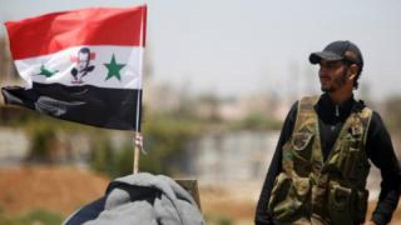 A Syrian army soldier stands next to a Syrian flag in Umm al-Mayazen, in the Deraa countryside, Syria (10 July 2018)
