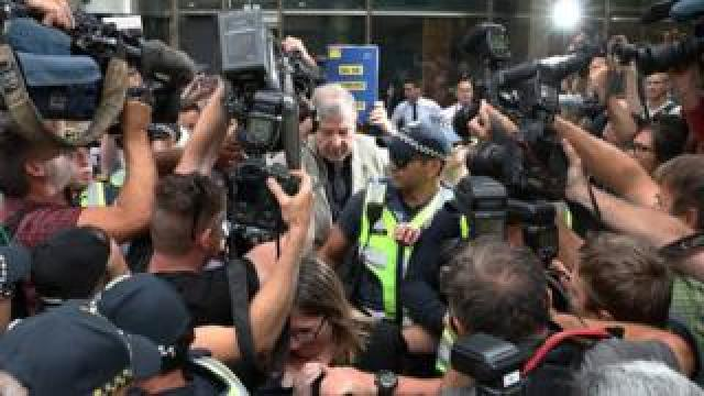 Cardinal George Pell swarmed by media as he leaves a court in February