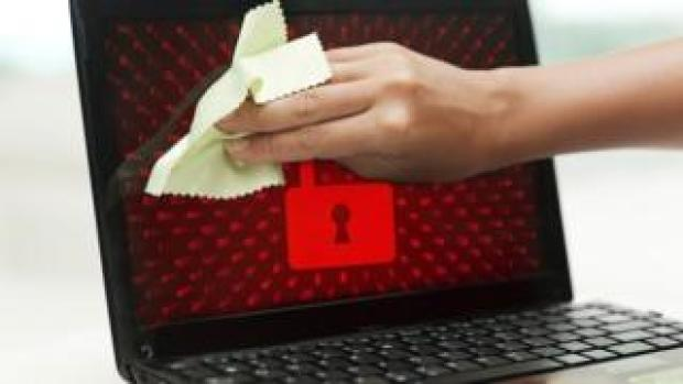 A composite image shows someone cleaning a laptop screen while a red padlock image is displayed on screen