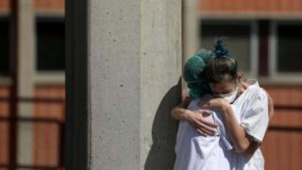 trump Medical workers hug each other outside the emergency rooms at Severo Ochoa Hospital during the coronavirus disease in Spain