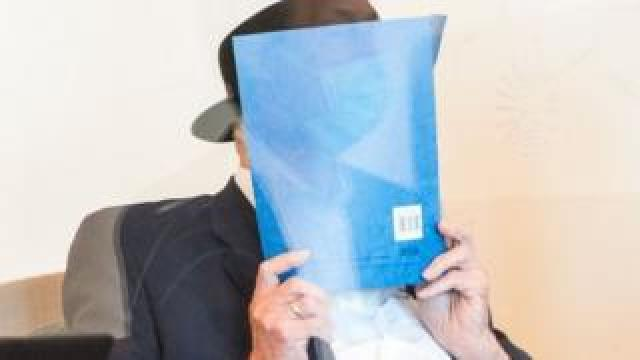 Bruno Dey holds a folder in front of his face in court on 23 July 2020