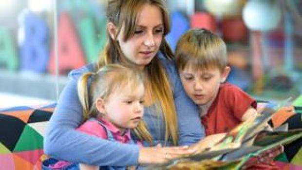 Au pair reading to two children