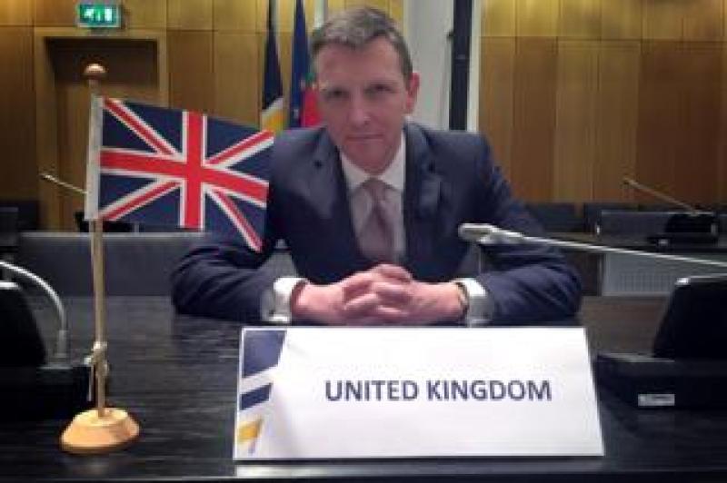 Mark Easton with UK flag in Europol boardroom