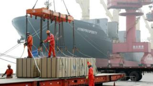 Workers load boxes onto a ship at Lianyungang Port.