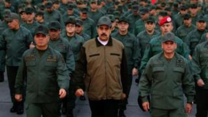 "This handout picture released by Miraflores Palace press office shows Venezuela's President Nicolas Maduro waving military troops accompanied by Defense Minister Vladimir Padrino (L) at the ""Fuerte Tiuna"" in Caracas, Venezuela on May 2, 2019"