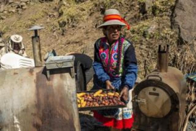 A woman cooks potatoes to complement the main dishes to feed the crowd
