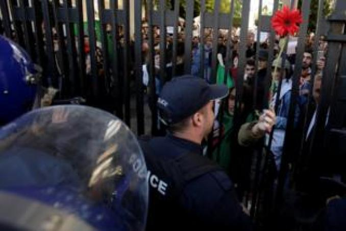 A student offers a flower to police while she protests with others inside a university campus against the fifth term of Abdelaziz Bouteflika in Algiers
