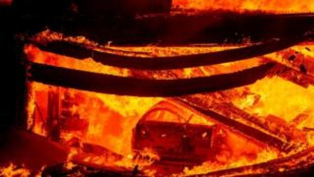 A car burns in a garage during the Hillside fire in the North Park, San Bernardino, California
