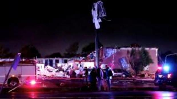 Emergency vehicles are seen near a partially collapsed building after a tornado touched down in El Reno, Oklahoma