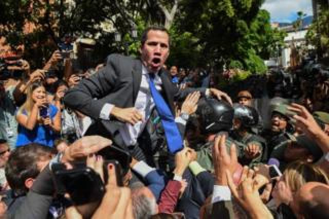 Venezuelan opposition leader Juan Guaido shouts as he is surrounded by journalists