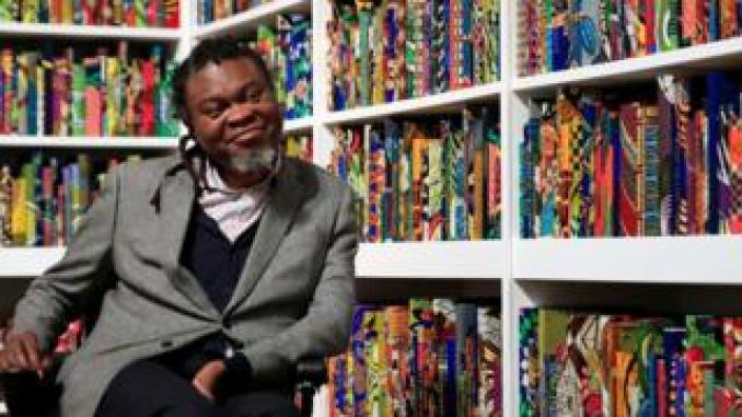 Yinka Shonibare poses with his art piece called The British Library at Tate Modern in London, UK - Monday 8 April 2019